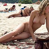 Youthful exhibitionists sunbathing undressed on the beach.