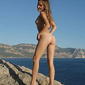 Seductive juvenile gal posing out of a swimsuit on the rocky beach.