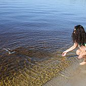 Brunette hair undressing beach.